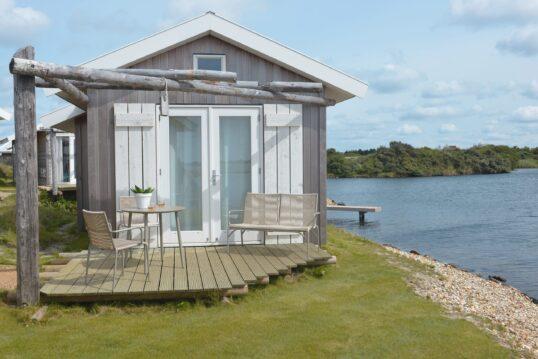 Skandinavisches Tiny House mit kleiner Terrasse und Sitzgruppe vor dem Hauseingang