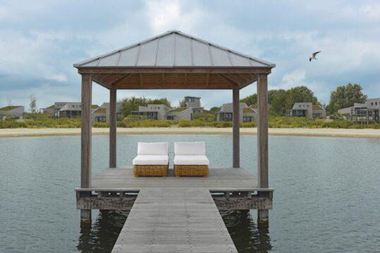 Terrassen Idee – Holzpavillon mit Liegen aus Rattan auf Steg vor Ferienhäuser...