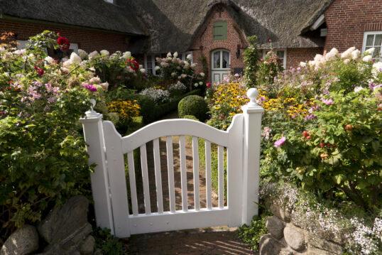Schönes Landhaus mit vielen bunten Blumen im Vorgarten