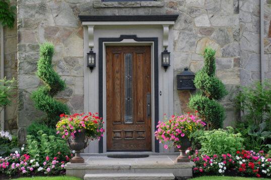 Schöner Hauseingang mit außergewöhnlicher Tür und Blumen