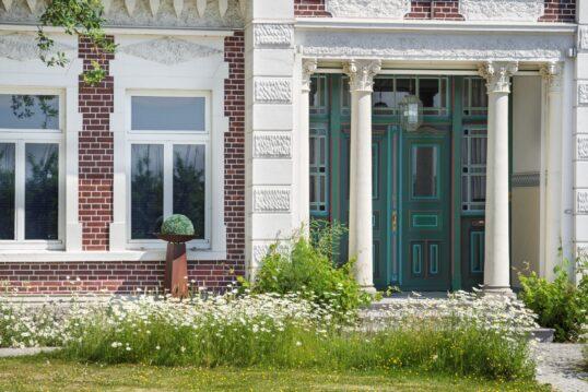 Schönes Haus mit Klinkersteinfassade und Säulen vor dem Hauseingang