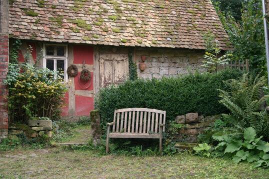 Garteninspiration – Altes Landhaus mit Hecke und gemütlicher Gartenbank