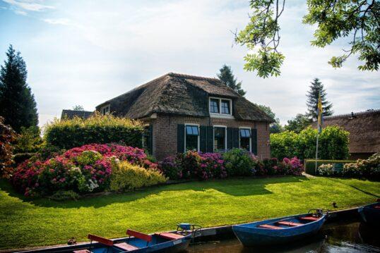 Wunderschöner Vorgarten mit Blumen und Hecken vor skandinavischem Haus mit Reetdach...