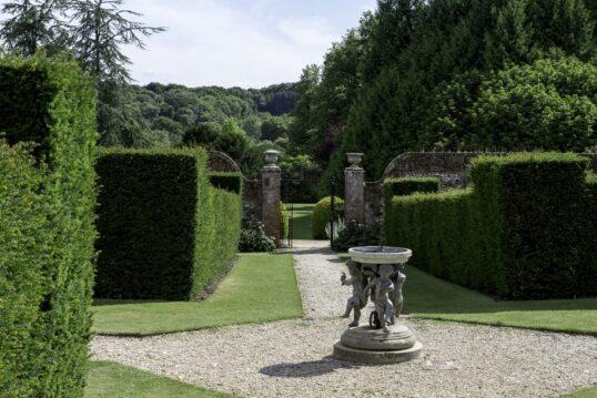Englischer Garten Idee – verspielte Sonnenuhr gehalten von Putten aus Stein a...