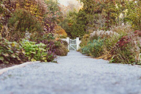 Seitlich bepflanzter Kiesweg zum Gartentor