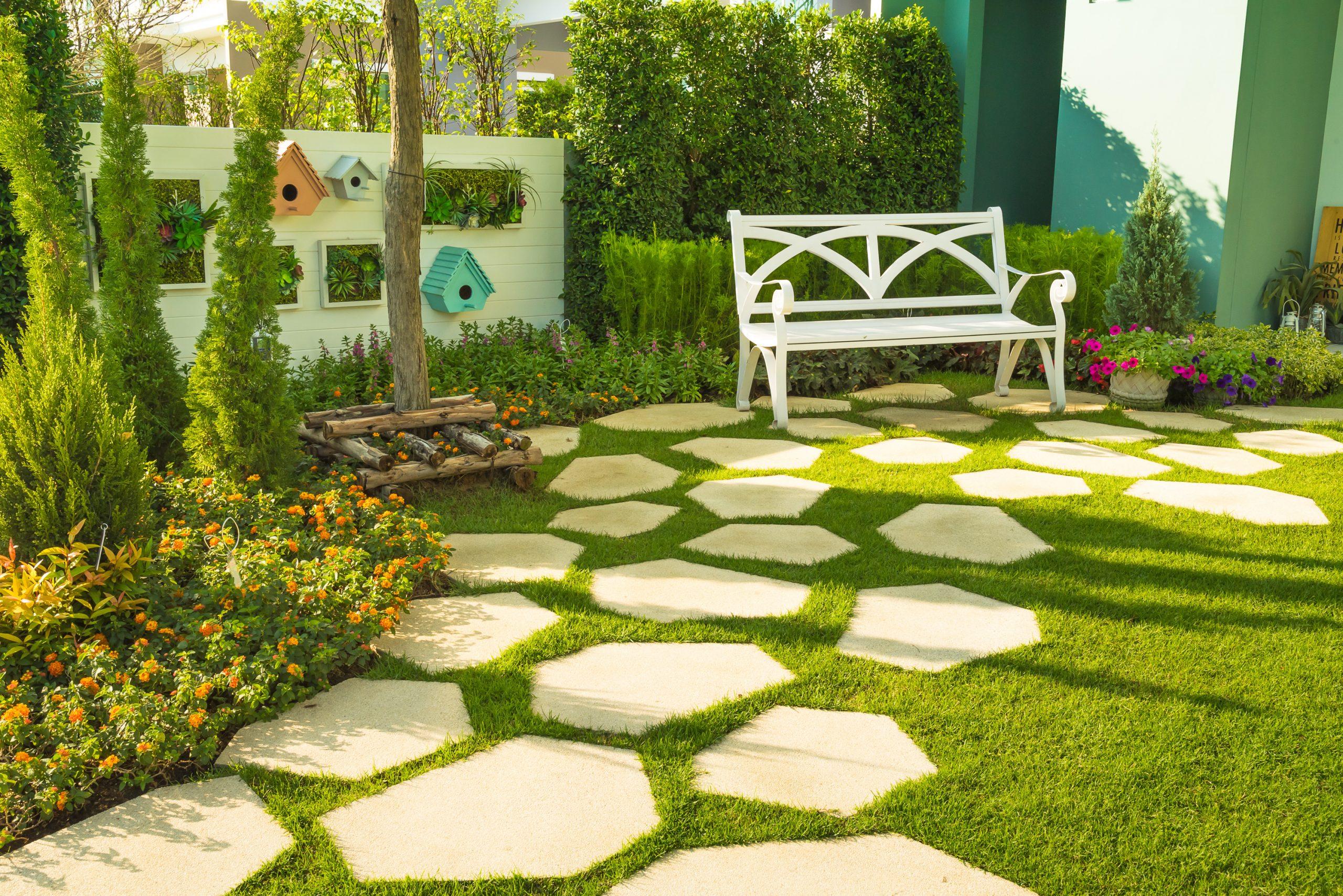 Schöner Garten mit Bank und großen Steinen als Gehweg