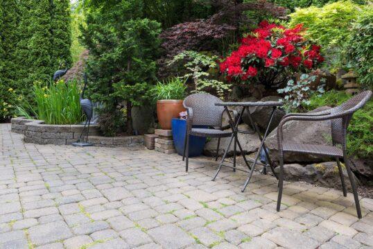 Gartenidee mit Sitzgruppe – Blumen und Gartenmöbel in Hof mit hoher Hecke als Sichtschutz