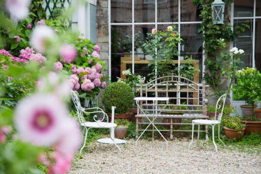 Gartenidee – Schöner Blumengarten vor großem Fenster mit Sitzgelegenheiten &#...