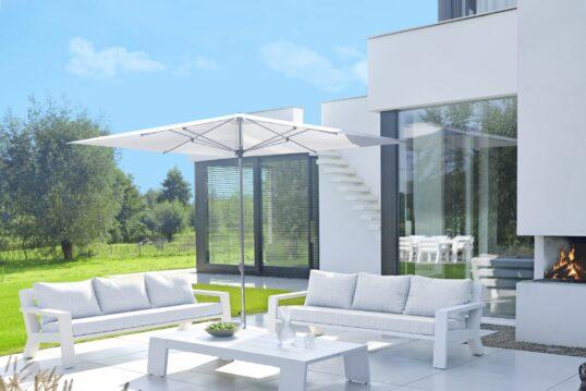 Weiß geflieste Terrasse mit Bänken und Tisch