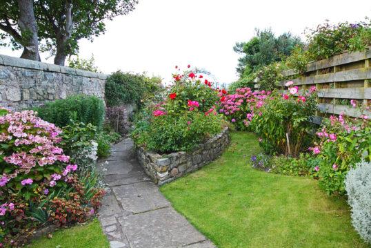 Landhaus Gartenidee – Garten mit Gartenweg aus Stein und hoher Steinmauer ...