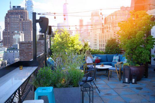Stylische Dachterrasse mit Sitzmöbeln und Pflanzen
