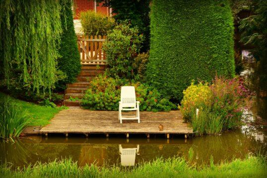 Gartenidee – Gemütliche Terrasse mit einem Gartenteich und Kunststoffliege