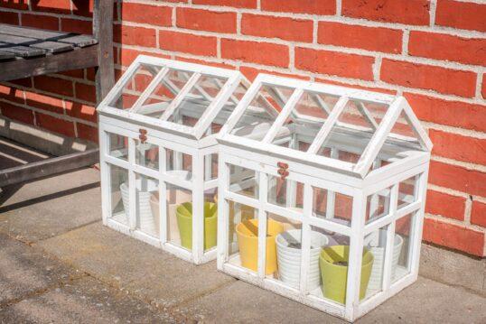 Gartenidee mit Mini-Gewächshäusern an der Hauswand als Aufbewahrung für Blumentöpfe...