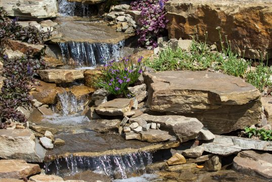 Gartengestaltung mit Wasser – Kleine Wasserfälle gestaltet mit Steinen und Bl...