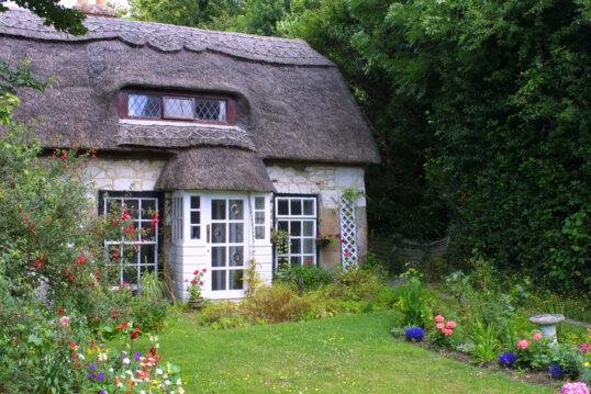 Weißes Reetdachhaus mit kleinem Garten und Spielwiese