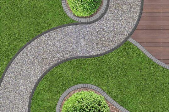 Gartenweg Idee – Modern gestalteter Gartenweg aus Kies umgeben von Grasflächen & einer Holzterrasse – runde Buchsbäume als Deko