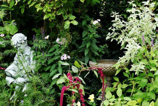 Gartendeko Idee – Beispiel mit Lesender Jungenskulptur und Vogeltränke inmitt...