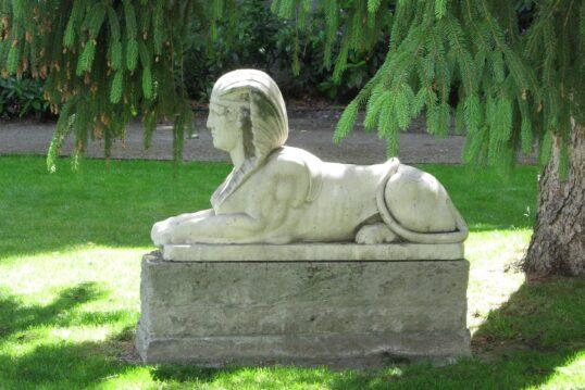 Sphinxskulptur unter einem großen Nadelbaum in einem Park