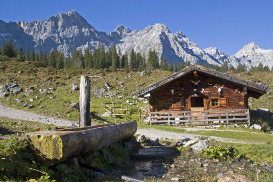 Wanderweg mit Berghütte mit Bachlauf und Holzbrunnen
