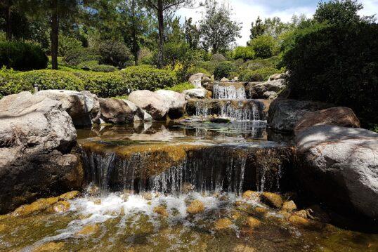 Idee für einen großen Garten – Beispiel mit langen Wasserfall mit großen Stei...
