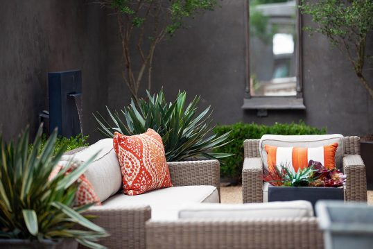 Terrasse im Innenhof Idee – Moderne Terrasse mit bequemen Rattanmöbeln  Wandb...