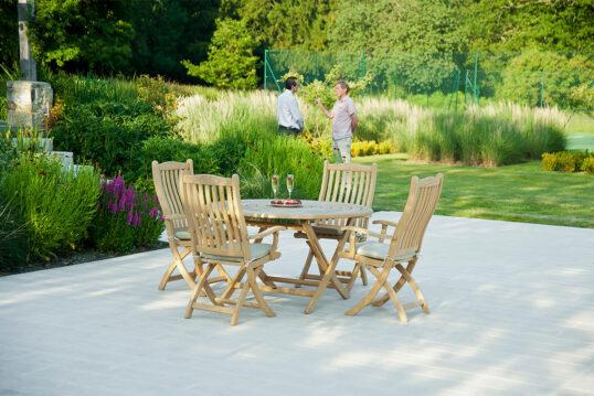 Idee für die moderne Terrassengestaltung – Holzsitzgruppe aus Stühlen und rundem Tisch für schöne Stunden auf der Terrasse – Blumen & Stauden auf Beeten
