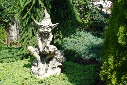 Gartengestaltung mit einer fantasievollen Skulptur als Dekoration zwischen zahlreic...