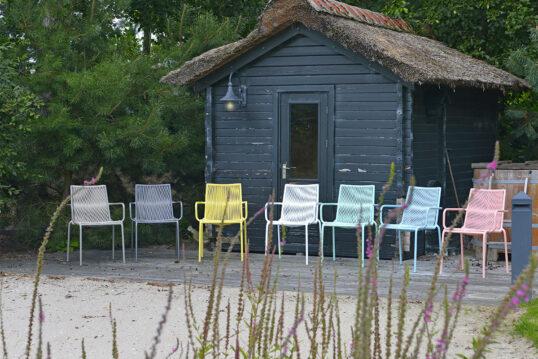 Terrasse mit Gartenhaus Idee – Kleine Strandterrasse mit farbenfrohen Stühlen...
