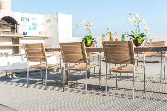 Mediterrane Dachterrasse mit hellen Stühlen und offenem Grillofen – Holzstühle & Holztisch mit Metallakzente – Terrassenpflanzen in Pflanzgefäßen