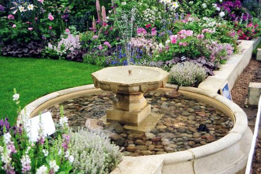 Idee für den Garten mit Kaskadenbrunnen aus Stein & vielen bunten Blumen &...