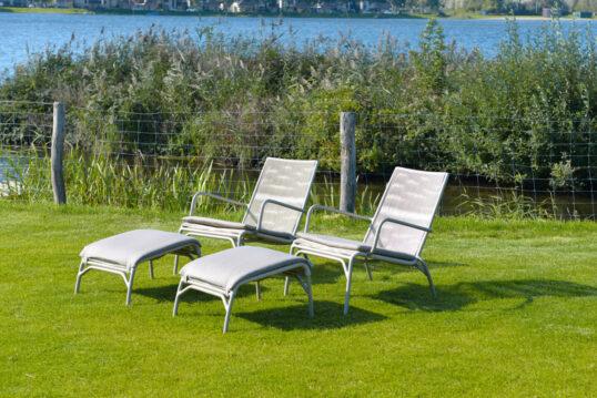 Gartenidee – moderne Liegen mit Hocker auf einer Wiese am See – Gartenz...