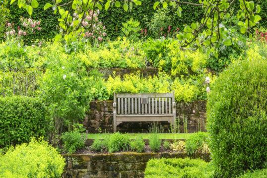 Idee für den Garten mit Hochbeeten mit Steinbegrenzung am Hang & Holzgartenban...