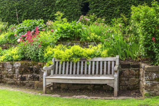 Romantische Gestaltungsidee für den Garten – Beispiel mit einer Holzbank vor ...