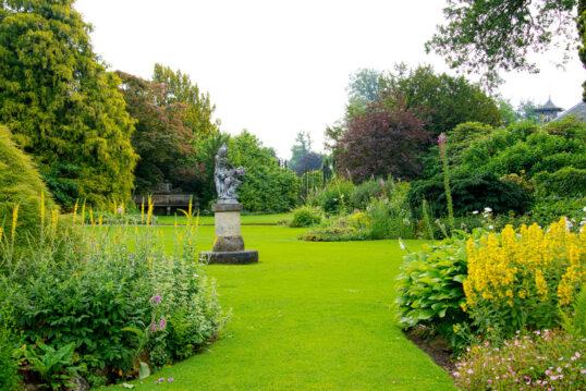 Idee für einen großen Garten mit Skulptur & Gartenruine – Beispiel für B...