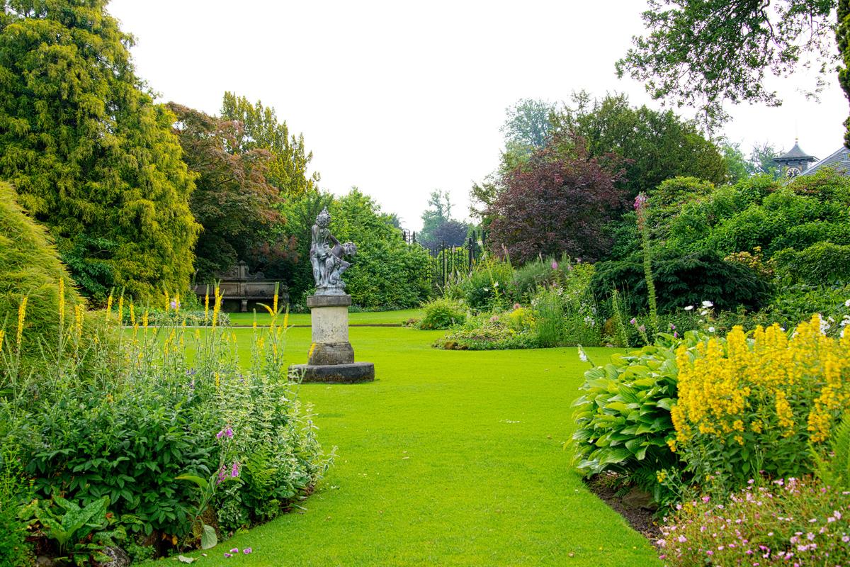 Gestaltung eines englischen Gartens mit Steinskulptur