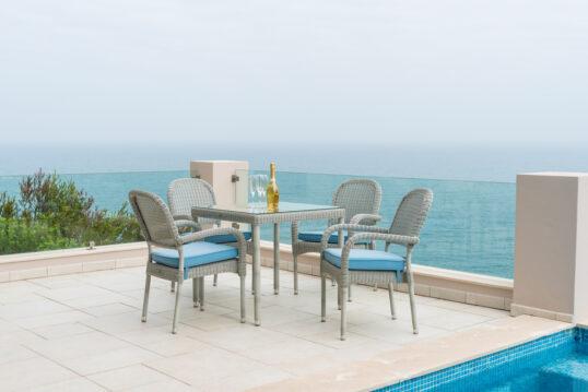Terrassen Idee mit einer Rattansitzgruppe in grau am Pool – Beispiel mit hell...