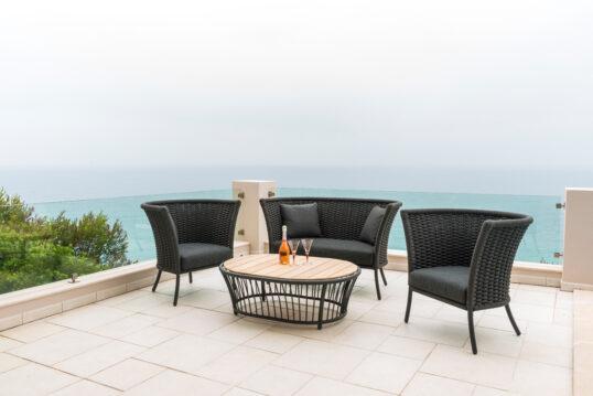 Moderne Idee mit einer schwarzen Sitzgruppe aus Polyrattan auf einer Terrasse ̵...