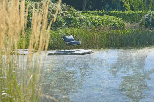 Gartenteich Idee – Kleiner Sitzbereich mit Suhl auf einem großen Stein am Gar...