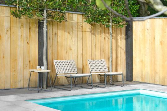 Gestaltungsbeispiel für einen Sitzbereich am Pool vor einem hohen Sichtschutzzaun a...