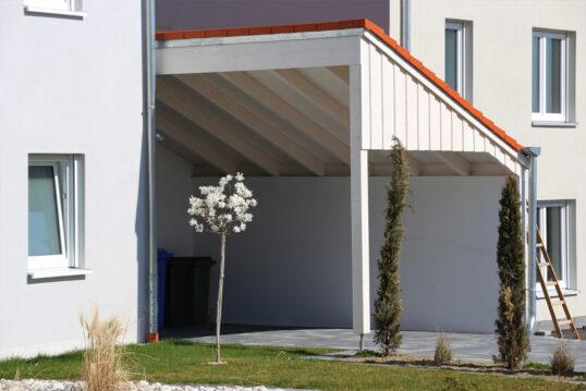 Moderner Anlehn-Carport in weiß mit roten Dachziegeln an der Hauswand als Gartenide...