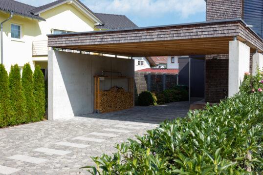 Moderne Vorgartengestaltung mit einem großen Carport mit Holzdach – Kaminholz...