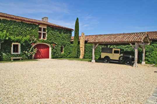 Mediterranes Landhaus mit rustikalen Carport als Vorgartenidee – Beispiel mit...