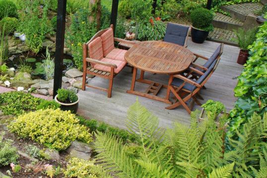 Terrassengestaltung in mediterraner Umgebung – Sitzgruppe aus Holz mit Polste...