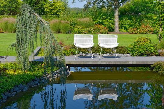 Gestaltungsbeispiel einer kleinen Terrasse am Gartenteich – zwei Retrostühle ...