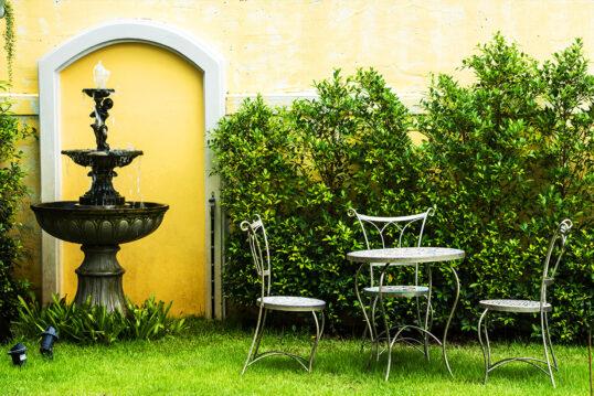 Gartenidee mit Sitzgruppe & Springbrunnen vor der Hauswand – Beispiel mi...