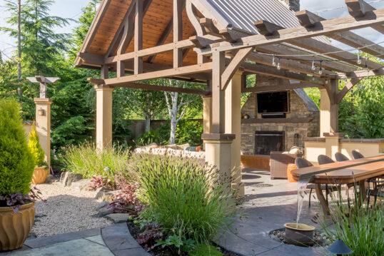 Große Landhausterrasse mit Überdachung als Gartenidee – Beispiel mit Sitzgrup...
