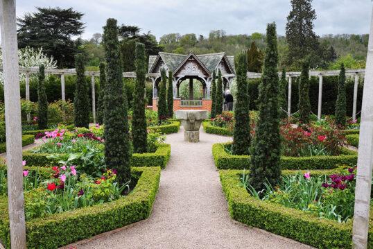 Landhaus Garten Idee mit vielen Hecken – Interessantes Gartenhaus  Steintisch & Blumen – schmale  hohe Bäume auf den Beeten