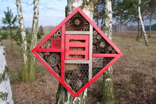 Idee mit einem roten Insektenhotel am Baum – Beispiel für die Gestaltung eine...