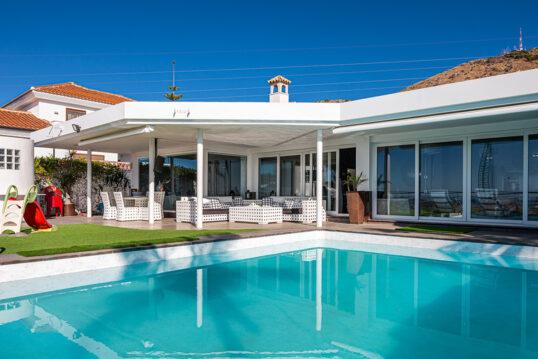Gartenidee – Überdachte Terrasse am modernen Wohnhaus mit Sitzgruppe & L...