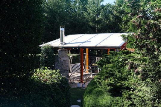 Gartenidee mit einer überdachten Terrasse – Beispiel mit Hollywoodschaukel au...